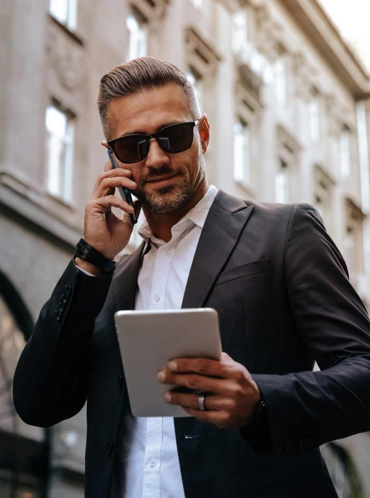 Image of a businessman working remotely and talking on the phone.