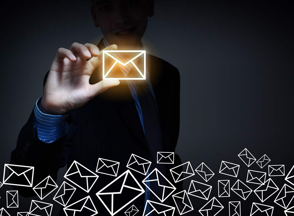 Image of a businessman holding a glowing envelope between his fingers, phishing email.