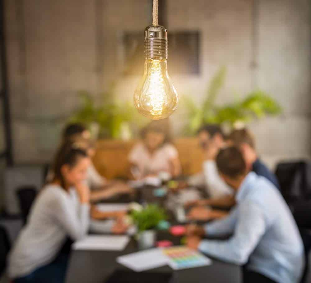 Image of a lightbulb with blurred images of co-workers collaborating in the background